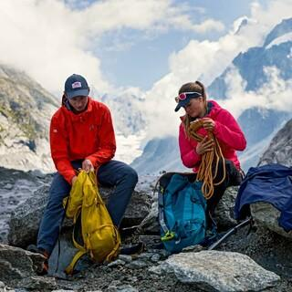 Zwei Personen am Berg packen ihre Rucksäcke, Foto: Mountain Equipment