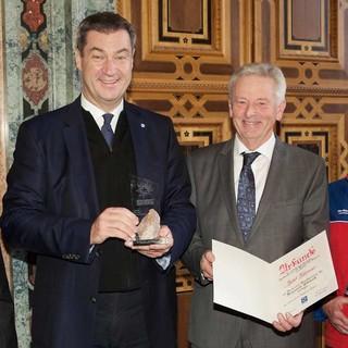 Josef Klenner nimmt die Urkunde von Markus Söder entgegen. Foto: Bergwacht Bayern