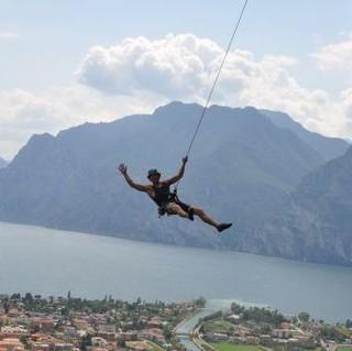 Ein Kletterer schwingt am Seil, den Gardasee immer im Blick. Foto: Lena Behrendes