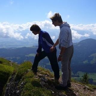 Zwei Teilnehmer werfen zusammen einen Blick über die Felskante hinab ins Tal. Foto: Archiv Jubi