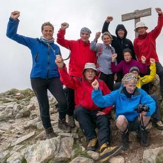 Stolzes Gipfelglück nach dem widrigen Aufstieg auf den Gipfel Bocca Muzzella auf 2210 m Höhe beim Lac de Melo mit Schnee, Wind und Nebel