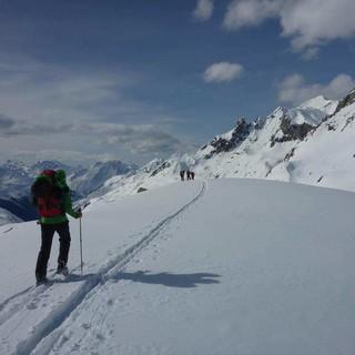 Skitourengeher*innen vor winterlicher Bergkulisse. Foto: Sarah Kästner