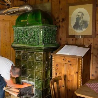 Totes Gebirge: Norbert Donza heizt den Ofen auf seiner Pühringer Hütte ein – ein gemütlicher Abend steht bevor. Foto: Iris Kürschner