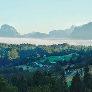 Bewaldete Hügel und kleine Ortschaften in den Belluneser Voralpen, dahinter die Schiara-Dolomiten. Foto: Joachim Chwaszcza