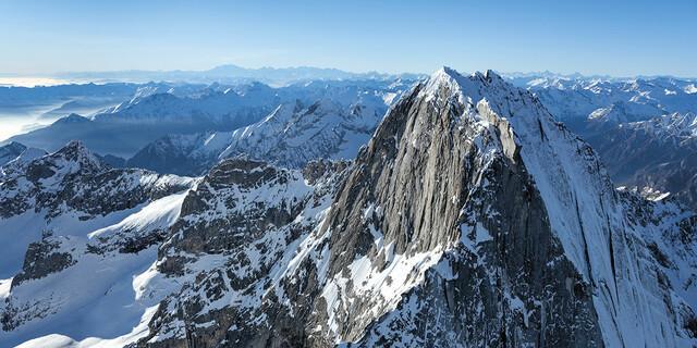 Oktober: Der Pizzo Badile (3308 m) von Osten, rechts die verschneite Nordostwand. Die berühmte Badile-Nordkante zieht nach rechts zum Bildrand, Bergell, Foto: Jörg Bodenbender