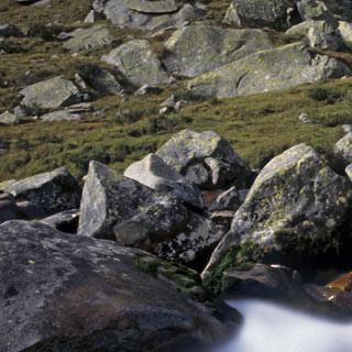 """Val Adamè - 6. Etappe: In kleinen Kaskaden fließt der Torrente Poia durch das Val Adamè. Immer wieder neue Blicke bieten sich dem Betrachter, der den kleinen Abstecher vom """"Sentiero 1"""" nach Norden auf sich nimmt."""