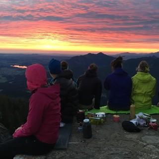 Gruppe genießt Sonnenuntergang im Gebirge. Foto: Kathrin Weber