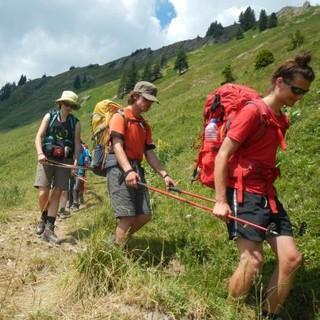 Eine Gruppe steigt gemeinsam mit Hilfsmitteln wie Stöcken über einen Wiesenhang ab. Foto: Eberhard Haeuschkel
