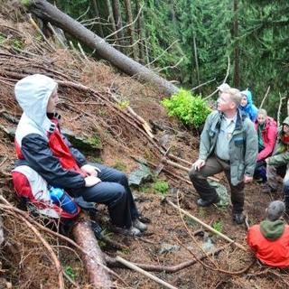 Förster führt Jugendgruppe im steilen Bergwald in ihre Aufgaben ein. Foto: JDAV/Johannes Branke