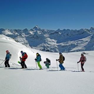 Gruppe im Tiefschnee bei Sonne und strahlend blauem Himmel. Foto: Franz