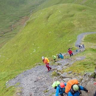 Respektvoller Einstieg - Mit Helm und Gurt in der Einstiegsrinne der Sharp Edge am Blencathra (868 m), schon bald wird es luftiger. Unten rechts der Scales Tarn (590 m).