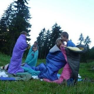 Kindergruppe beim Schlafsackhüpfen auf der Wiese. Foto: Claudia Wegmann