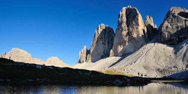 Dolomiten wie sie sein sollen: Die Nordwände der Drei Zinnen über einem See an der Langalm, Foto: Ralf Gantzhorn