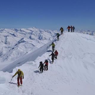Skirunde Großvenediger: Der etwas luftige Gratübergang zum Gipfelkreuz des Großvenedigers, links der Bildmitte der Großglockner. Foto: Stefan Herbke