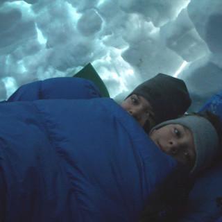 Zwei Jungen kuscheln sich unter der Iglukuppel in Ihren Schlafsack. Bild: JDAV/Wahl