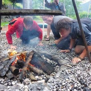 Drei Jungs pusten fleißig beim Lagerfeuer Anheizen. Foto: Sarah Kästner