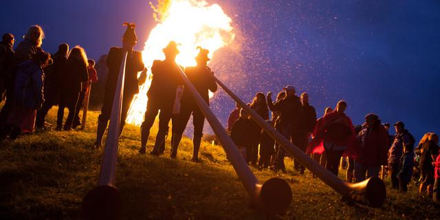Alphornbläser während der Sonnwendfeuer auf der Kampenwand. Foto: Kampenwandseilbahn GmbH / Eric Zbil