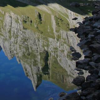 Berge im Fählensee – und natürlich dort, wo sie hingehören. Messerscharf spiegeln sich Almhütten und Kletterwände im Wasser. Ein zauberhafter, mystischer Moment der Stille, bevor die ersten Wanderer von der Bollwees herkommen. Foto: Silvia Schmid