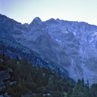Lago d'Aviolo - 2. Etappe: Dunkel liegt der Lago d'Aviolo im Morgengrauen unter den noch düstereren Baitone-Nordwänden. Im zentralen Teil der Gruppe herrscht das Ambiente von Wildnis und Abenteuer.