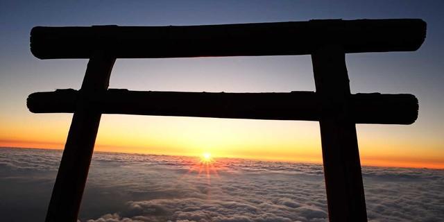 Am heiligen Berg Fuji steigt die Sonne unter einem Torii-Bogen aus den Wolken. Foto: Norbert Eisele-Hein