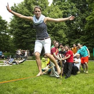 Ein Mädchen balanciert auf der Slackline, welche die Gruppe im Hintergrund auf Spannung hält. Foto: Olszewski