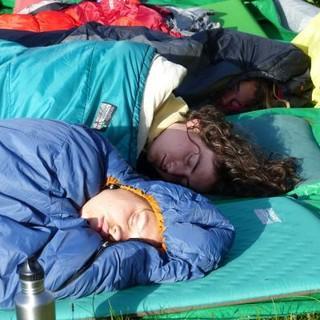 Die ersten Sonnenstrahlen scheinen auf die noch schlafenden Teilnehmer*innen in ihren Schlafsäcken. Foto: Sabine Fröhlich