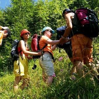 Die Teilnehmer*innen unterstützen sich gegenseitig beim Erklimmen einer steilen Bergwiese. Foto: Archiv Jubi