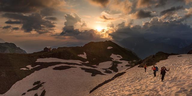 Beim Aufbruch von der Claridenhütte lässt die Morgensonne die Wolken aufleuchten. Foto: Ralf Gantzhorn